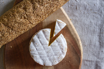 The Swiss Camembert formed cheese and a triangular piece of cheese on a wooden textured board and a grain baguette on a woven canvas background.