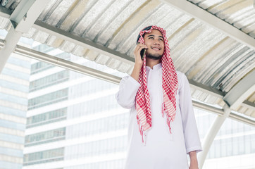 muslim businessman in traditional clothes talking on cell phone