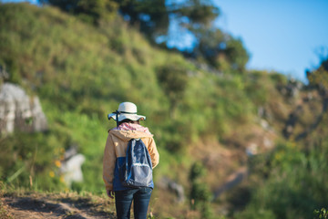 young girl with backpack enjoying sunrise on peak mountain.