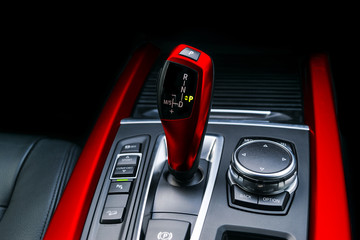Red Automatic gear stick (transmission) of a modern car, multimedia and navigation control buttons. Car interior details. Transmission shift.