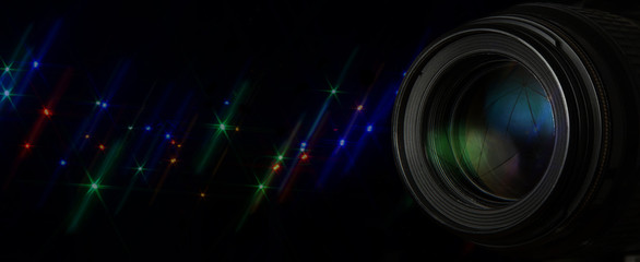 Photo lens with glittering stars flash over black background