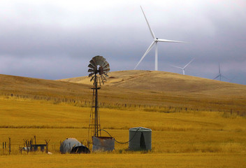 An old windmill stands in front of wind turbines in a paddock near the Hornsdale Power Reserve, featuring the world's largest lithium ion battery made by Tesla, located on the outskirts of the South Australian town of Jamestown