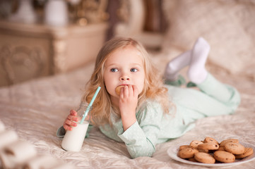 Funny girl 3-4 year old eating cookies and drinking milk in bed. Good morning. Breakfast.