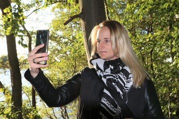Frau macht ein Selfie von sich mit dem Smartphone in der Natur, Konzept Lifestyle