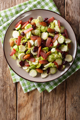 Delicious salad from Brussels sprouts, dried cranberries, almonds and ham close-up. Vertical top view