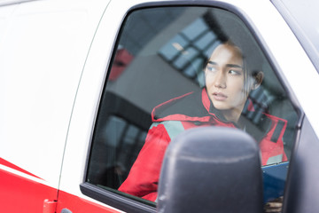young Asian female paramedic sitting in ambulance and looking away