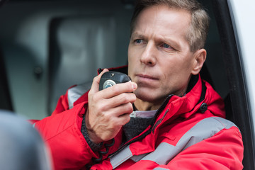 handsome middle aged male paramedic talking by portable radio while sitting in ambulance