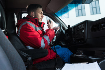 young handsome male paramedic talking by portable radio
