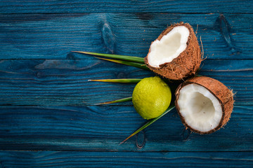 Coconut and lime. Fresh fruits. On a wooden background. Top view. Free space for text.