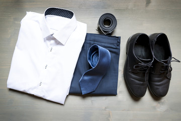 Folded businessman's clothes and shoes. White shirt, blue pants, leather belt and blue tie