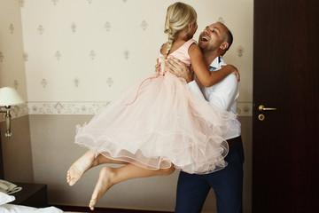 Happy father holds little daughter on his arms standing in the room