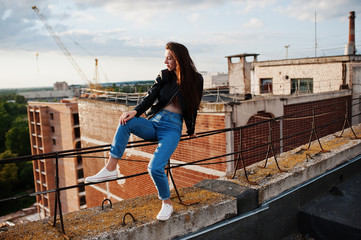 Portrait of a gorgeous young woman in black leather jacket, jeans and sneakers sitting on handrails on the roof with picturesque view of a park.