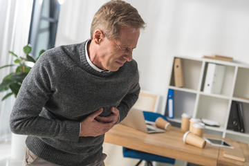 middle aged man having heart attack in his office