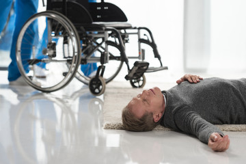 unconscious middle aged man lying on a floor in hospital