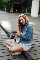 Young smiling woman sitting on a wooden floor using a digital camera