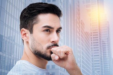 Making plan. Handsome young bearded man wrinkling forehead and covering his mouth while looking forward