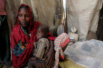 Falmata Alwana, an internally displaced person living in Bama camp, Nigeria, poses for a picture with one of her children in her shelter