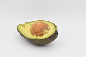 Halved avocado with nut on white background