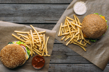 top view of hamburgers, french fries and sauces on baking paper on wooden tabletop