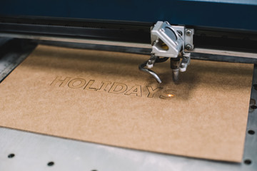 """Industrial laser engraving word """"holiday"""" on a cardboard, process"""