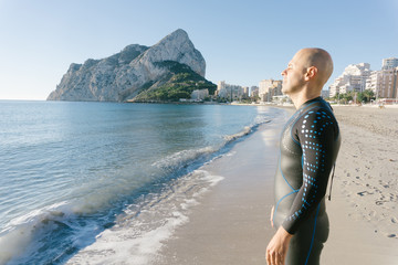 Diver in wet suit standing on beach