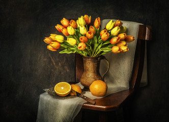 Classic still life with bouquet of tulips flowers placed on rustic wooden chair with fresh oranges and scarf