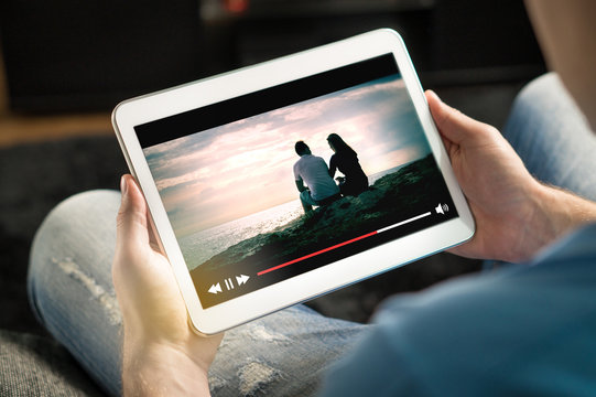 Online movie stream with mobile device. Man watching film on tablet with imaginary video player service.