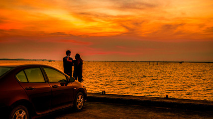 Silhouette of happiness couple standing by the car at the seaside at sunset. Beautiful orange sky and clouds