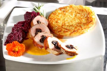 Mit Pflaumen gefülltes Schweinefilet im Schinkenmantel mit Rotkohl und Rösti auf Kürbissauce