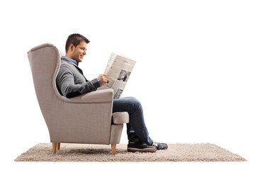 Young guy seated in an armchair reading a newspaper