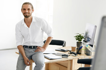 Confident Male Worker Standing In Office