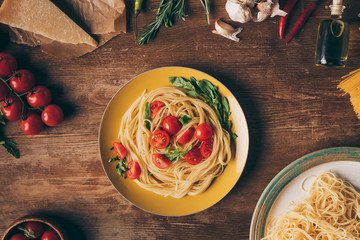 flat lay with traditional italian pasta with tomatoes and arugula in plate on wooden table with ingredients
