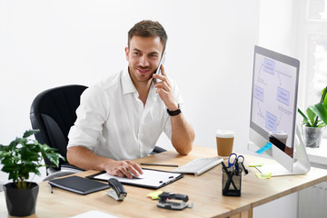 Businessman Talking On Phone At Workplace