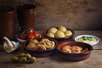 Rustic party appetizers such as baked olives, prawn shrimps, potatoes, tomato and garlic dip, spanish tapas served on a wooden board, dark background with copy space