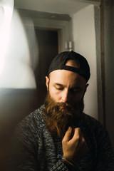 Bearded man in cap posing inside