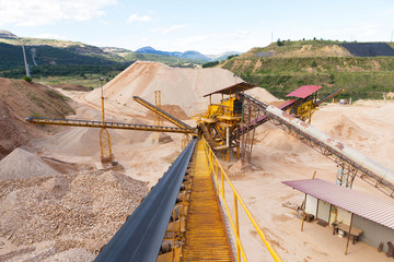 Gravel pit in mountain area with machinery and distribution tapes gravel according sizes, lots of gravel and sand for construction industry