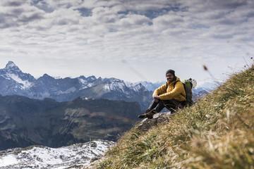 Germany, Bavaria, Oberstdorf, smiling hiker sitting in alpine scenery