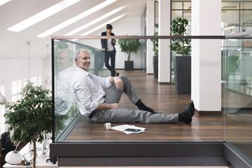 Mature businessman sitting on floor taking a break, drinking coffee