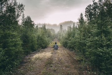 Man sitting on path in forest
