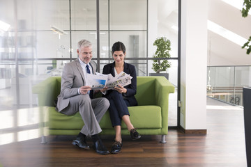 Businessman and woman sitting on couch in office looking at documents