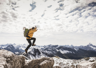 Germany, Bavaria, Oberstdorf, man jumping on rock in alpine scenery