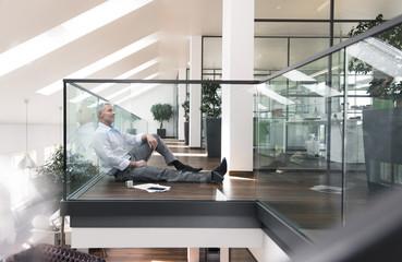 Businessman sitting on floor in the office, taking a break