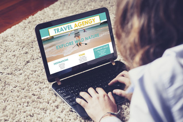 Travel agency website in a laptop screen while woman search for vacation destination.