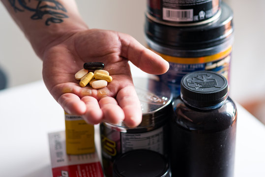 Close up of bodybuilding pills in hand of a man