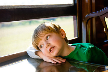 adorable toddler boy looking out window dreaming as riding on train