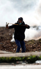 A Palestinian protester uses a slingshot to hurl stones towards Israeli troops during clashes in the West Bank village of Qusrah