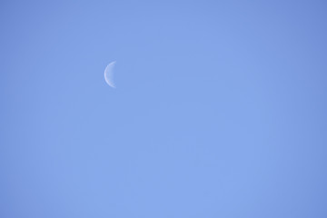 Waning Crescent Day. Lunar phase, bright illuminated moon during the day.