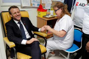 A nurse takes blood for a HIV test to French President Emmanuel Macron as he visits the Delafontaine Hospital in Saint-Denis as part of the World AIDS Day