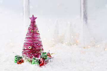 Winter scene of pink retro Christmas tree surrounded by gifts in front of an window.