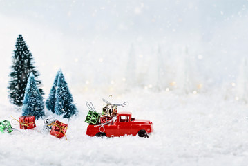 1950's antique vintage red truck hauling a Christmas gifts home through a snowy winter wonder land with pine trees. Extreme shallow depth of field with selective focus on vehicle.